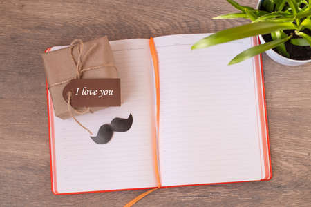 An open notebook with a gift box, a banner with gratitude and a Declaration of love. Black mustache. Houseplant. Dark, wooden background. Space for text. Horizontal photo