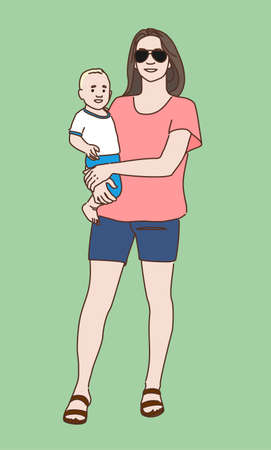 A young woman in glasses, T-shirt and shorts is holding a small child in her arms.
