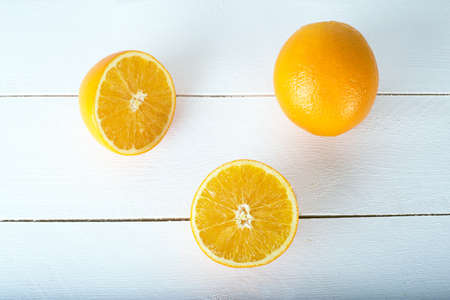 sweet segments: an orange on a white wooden background