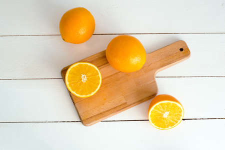 sweet segments: oranges and on a wooden borad on a white wooden background Stock Photo