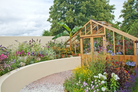 Tranquil garden with a greenhouse Standard-Bild