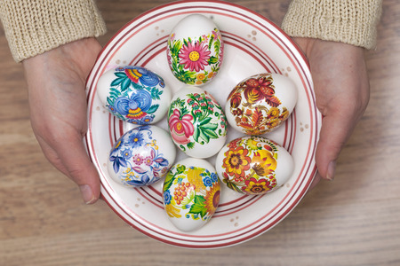 Decorated Easter eggs in a plate hold by two hands Standard-Bild
