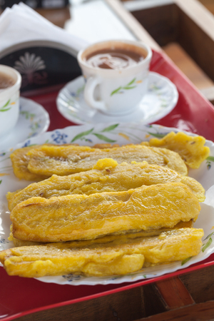 Yellow sliced plantain banana fry, fried in pan with hot coconut oil and two cups of masala tea in Kerala, India