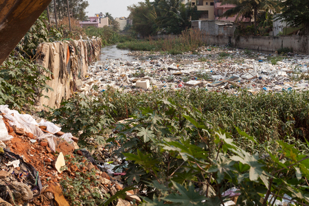 Big rubbish dump by the road in the river, ecological disaster Standard-Bild