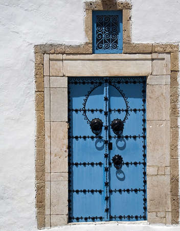 Blue tunisian door at sunlight photo