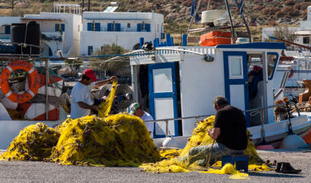 FOLEGANDROS, GREECE, MAY 2011  Unidentified Fisher men at work and inspecting his nets in the harbor on the aegean sea in folegandros, Greece, 2011