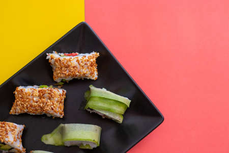 Top down closeup view of a sushi plate with sesame seeds and cucumber wrap on a combination of vibrant pink and yellow colors. Right area left for copyspace Stok Fotoğraf