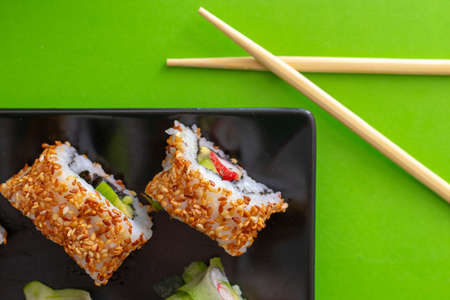 Top down view of a black square plate with multiple sushi rolls with sesame seeds and cucumber on green simple background with crossed chopsticks