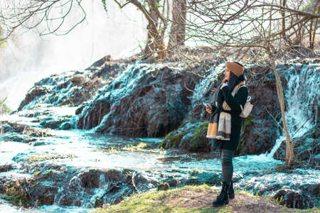 Girl traveller standing on a mossy patch of grass , cold river flowing in the background. Kravice waterfall in bosnia on a cold winter day Фото со стока - 148458779