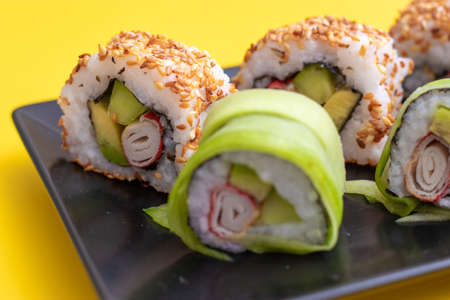Closeup view of a california sushi roll with sesame seeds and surimi in a sushi set on black plate and bright yellow background Stok Fotoğraf