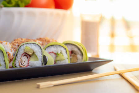 Homemade california and cucumber sushi rolls with surimi fake crab meat, avocado and fried sesame seeds. Served in two rows on a black plate at home. Chopsticks on table, bright sun background glare Stok Fotoğraf