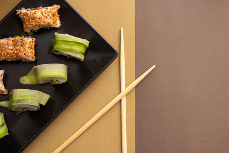 Homemade california and cucumber sushi rolls with sesame seeds on a black square plate on a brown beige background with wooden chopsticks Stok Fotoğraf