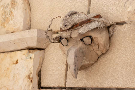 Old antique statue resembling a plague doctor from the middle ages. Seen on the outside of an old building on the island of Hvar Stock Photo