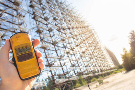 Hand holding a yellow dosimeter indicating radiation on the screen. Enormous Duga radar complex seen stretching to infinity in the distance. Danger of radiation in the exclusion zone Stock Photo