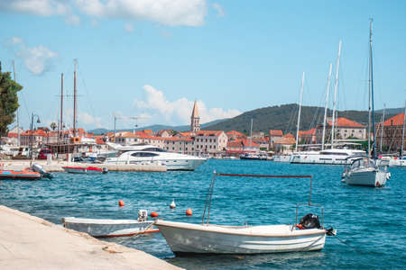 Panoramic waterfront view of the seaside of Starigrad, Hvar. Old boats in the front docked, houses and the famous church belltower seen in the distance