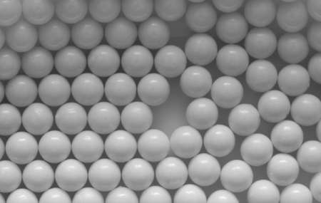 Closeup of white plastic bb's lined up on flat background