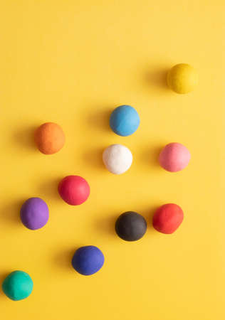 Many different colored plasticine balls on a yellow background. Colorful top down view, hand rolled childrens toys Stock fotó