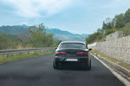 Rear view of a black modified old italian car driving through south Croatia. Crossing a hill with mountains in the distance on a nice sunny day