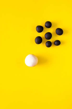 One big white ball and many black smaller plasticine balls in a group. Concepts of race and racism. White power and privilege. Area left for copyspace on yellow background