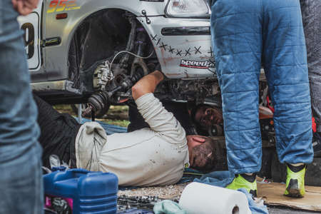 Skradin, Croatia, June 2020 Mechanics under a dissasembled front of the car, working on the racecar before a hillclimb. Parked in the paddock, hectic race environment 新闻类图片