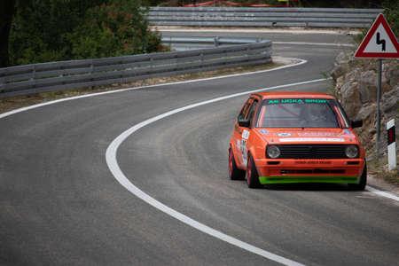 Skradin Croatia June 2020 Orange modified Volkswagen Golf going uphill on a race