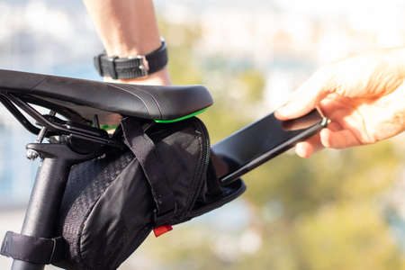 Man putting his smartphone inside a small black pouch for storage under the seat of a bicycle