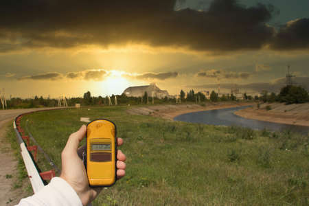 Hand holding a yellow dosimeter showing high radiation, metal sarcophagus of the chernobyl ruined reactor in the distance during a late afternoon golden beautiful sunset lining up perfectly.