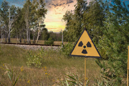 Yellow warning sign indicating radiation in the chernobyl exclusion zone, dangerous red forest in the background. Late afternoon beautiful golden sunset time Stock fotó