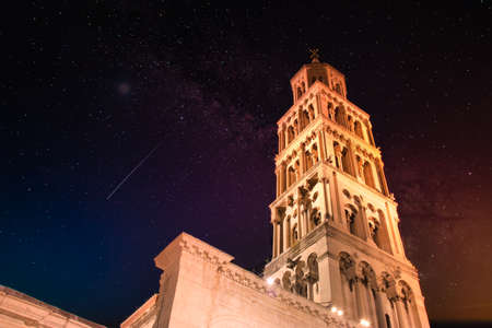 Saint Dominus belltower seen from below, long exposure, illuminated by orange lights at night, beautiful colorful night sky with purple and orange colors Stock Photo