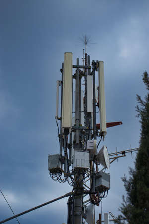 Closeup of a 4g 5g communications mobile tower on top of a hill, antennas for broadcasting signals