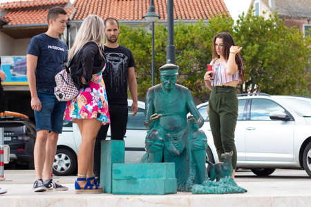 Primosten Croatia July 2020 Several tourists examining the statue of an old fisherman holding a net, small metal cat next to him