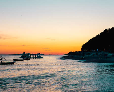 Sunset on a sandy beach in primosten, croatia. Dark with no light, outlines of the hill and small water park Stock Photo