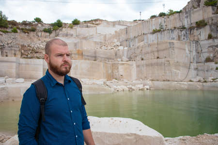 Bald bearded man standing in an abandoned stone quarry on the island of brac, croatia. Looking into the distance with a serious concerned look