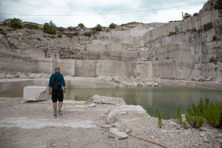 Man seen from behind wearing a backpack walking through an abandoned quarry on the island of brac, Croatia