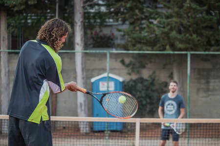 Man with longer hair seen from behind swining his racquet forehand to hit the ball, playing tennis outdoors with a friend. Ball seen blurred flying fast in the air 免版税图像