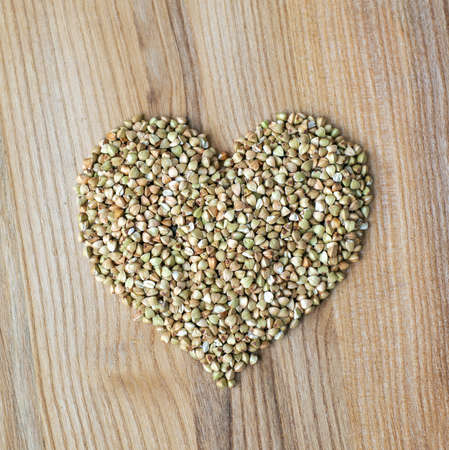 Heart shape made of buckwheat groats on wooden background. Close up, top view, high resolution product