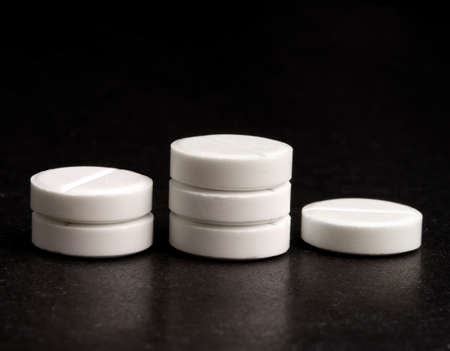White tablets on a black background, stand like steps of a pedestal