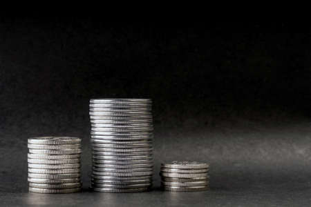 three piles of steel coins on a black background. Imagens