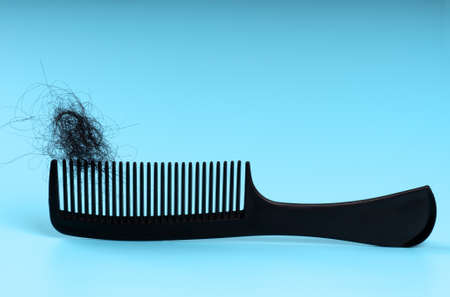 comb with long fallen hair on a blue background.