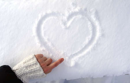 Hand draws a sign of the heart on the snow.