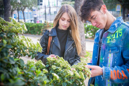 Outdoor, a young italian man and woman are couple in spring day in the park look over the hedge at the park flowers whit three and green whit flower