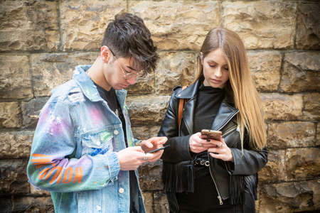 Italian woman and man with black leather jacket and denim jacket with many writings use their mobile phone in a small street of an Italian old town
