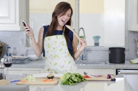 persona cantando: Ama de casa linda que se divierte en la cocina Foto de archivo