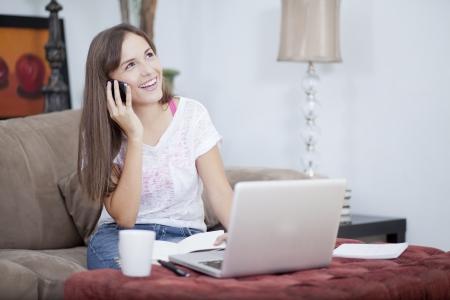 hablando por celular: Mujer joven que habla con un cliente Foto de archivo