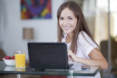 Beautiful young woman working from home while eating breakfast