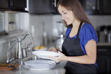 Young beautiful woman washing dishes in the kitchen photo
