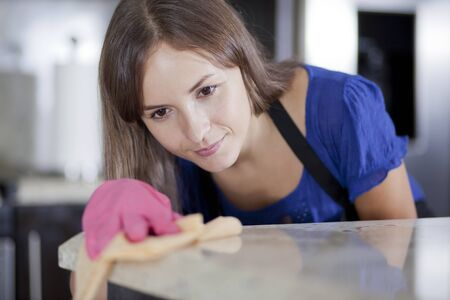 Cute young housewife cleaning a counter top in the kitchen Stok Fotoğraf