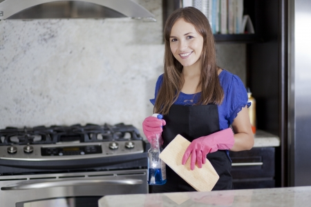 stove: Cute woman cleaning the kitchen