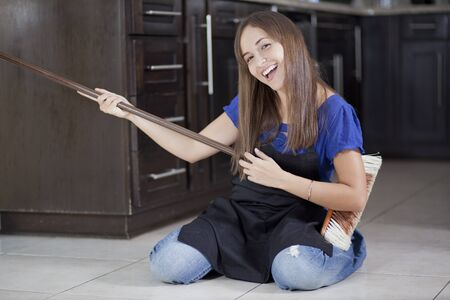 Cute young housewife having fun with a broom while sweeping the house photo