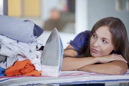 Overwhelmed young woman looking at a pile of clothes that need to be ironed Stock Photo